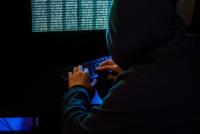 Cyberkriminalitität: Hacker im dunklen Raum am Computer