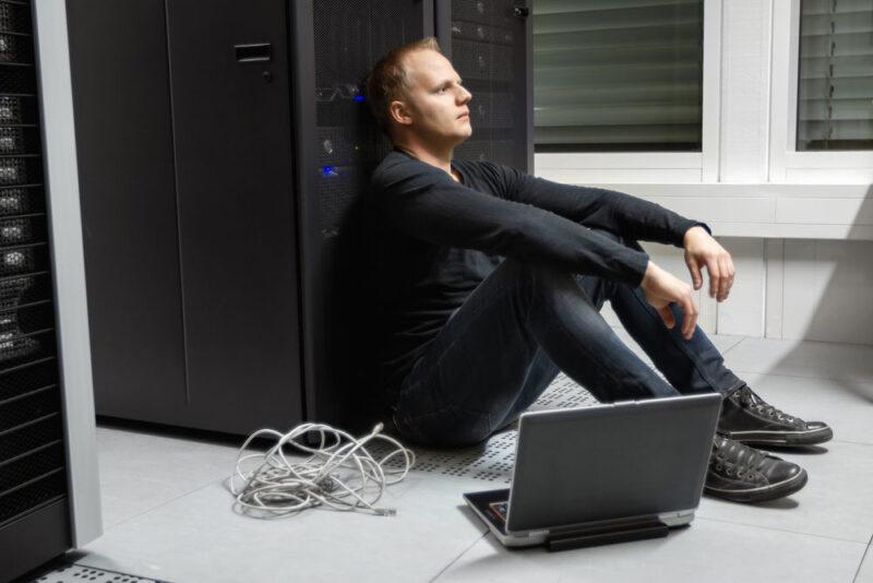 Hochverfügbarkeit in der IT: Frustrierter auf dem Boden vor einem Server sitzender IT Techniker