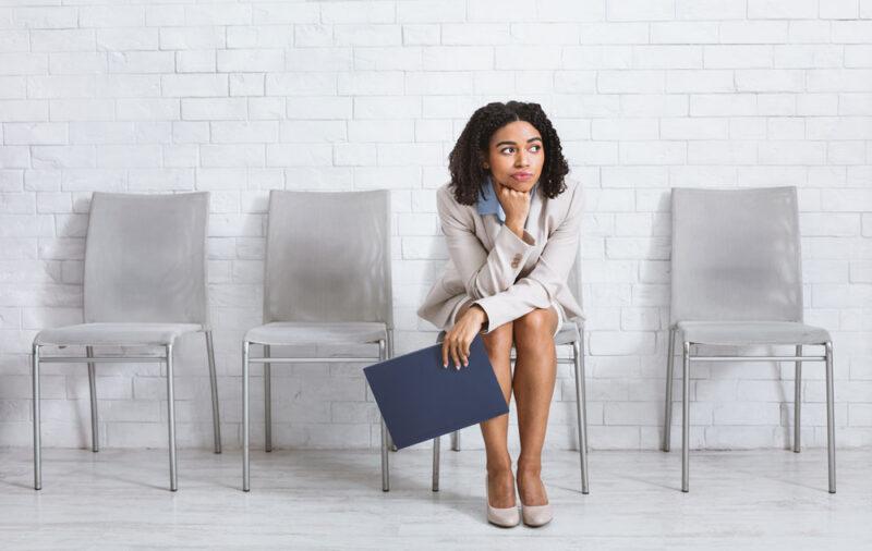 Gelangweilte Bewerberin sitzt allein auf einem Stuhl im Wartebereich