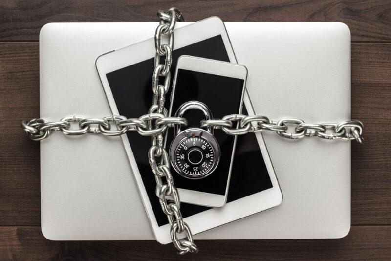 Tablet, Smartphone und Laptop mit Kette gesichert als Symbolbild für IT-Security