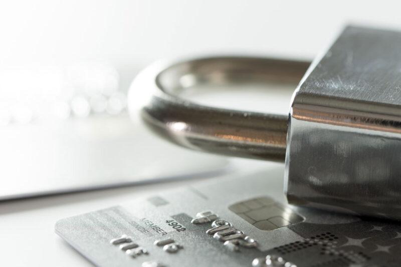 Nahaufnahme eines silbernen Vorhängeschlosses auf einer silbernen Kreditkarte