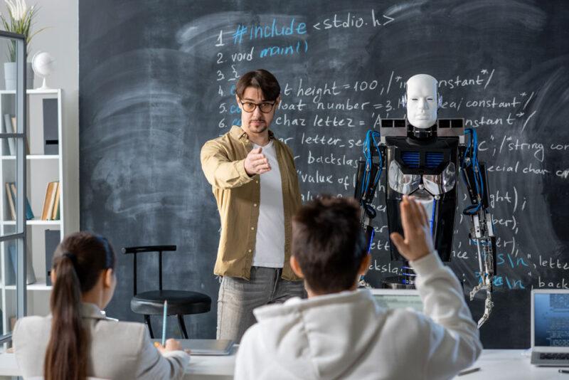 Lehrer unterrichtet gemeinsam mit einem Roboter der Symbolisch eine künstliche Intelligenz darstellt